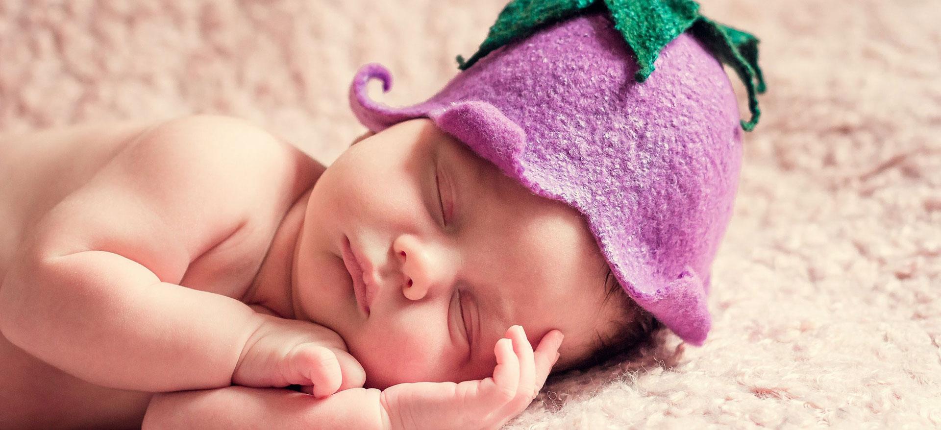 帽子を被ってすやすやと眠る裸の赤ちゃん