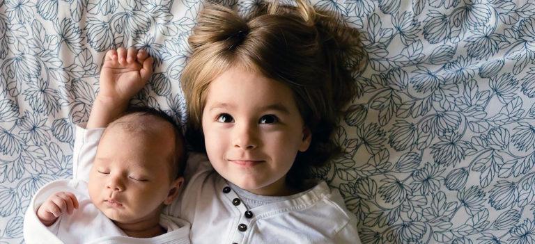 寝転がる赤ちゃんとお姉ちゃん