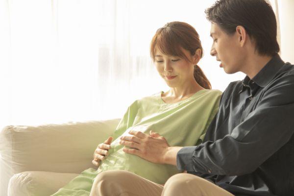 ソファーで幸せそうにお腹をさする夫と妊婦