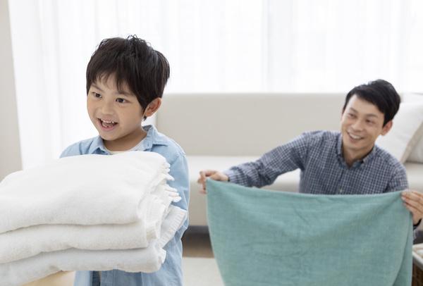 洗濯物をたたむ男の子とパパ